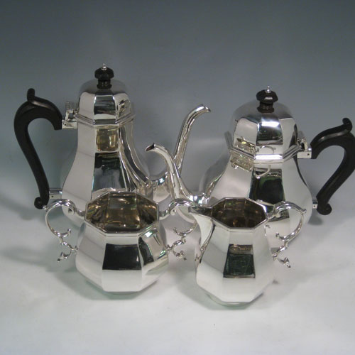 Sterling silver tea and coffee service, consisting of a coffee pot, teapot, sugar bow, and cream jug, having panelled bodies, wooden handles and finials, and hinged domed lids. Made by Garrards of London in 1957. Height of coffee pot 22 cms (8.75 inches), length of teapot 26 cms (10.75 inches). Total weight approx. 2,350g (75.8 troy ounces).