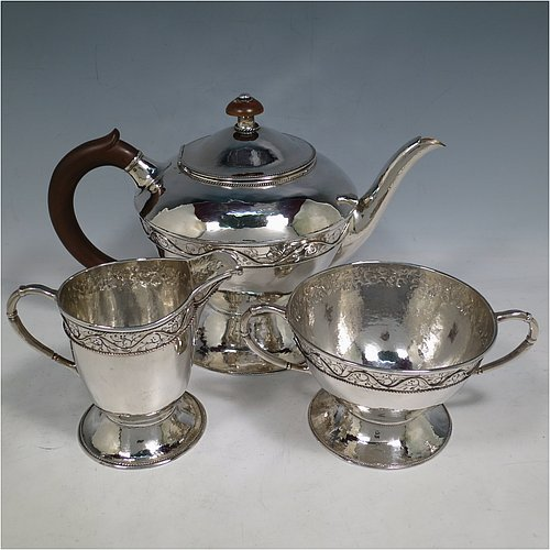 A Sterling Silver Arts and Crafts style three-piece tea set, having round bodies with hand-hammered decoration, with applied and hand-chased bands of floral work, the teapot with brown-stained wooden handle and finial, and the sugar and creamer with cast rounded handles, all with applied rope-twist borders, and all sitting on spreading pedestal feet. Made by Harold Edwin Landon of Chester in 1933. The dimensions of this fine hand-made Arts and Crafts tea set are height of teapot 18 cms (7 inches), length 28 cms (11 inches), diameter 15 cms (6 inches), and with a total weight of approx. 992g (32 troy ounces).