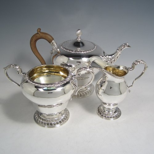 Sterling silver heavy three-piece tea set, consisting of teapot, sugar bowl, and cream jug, in a round baluster style having plain bodies, with applied gadroon borders, cast scroll handles and gold-gilt interiors, the teapot with a hinged lid and flame finial, a wooden insulated handle, and all sitting on pedestal feet with hand-chased swirl fluting. Made by Charles Townley and John Thomas, of London in 1913. The dimensions of this fine hand-made silver tea set are height of teapot 18 cms (7 inches), length 26.5 cms (10.5 inches), and it weighs a total of approx. 1,490g (48 troy ounces).