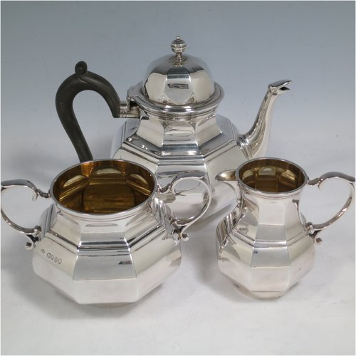 An Antique Victorian Sterling Silver three-piece bachelor tea set, having hexagonal panelled bodies, the teapot with a domed hinged lid with cast finial, a black wooden scroll handle, the cream and sugar bowl with gold gilt interiors and scroll handles, and all sitting on collet feet. Made by Joshua Vander of London in 1889. The dimensions of this fine hand-made antique silver tea set are height of teapot 14 cms (5.5 inches), length of teapot 17.5 cms (7 inches), with a total weight of approx. 589g (19 troy ounces).