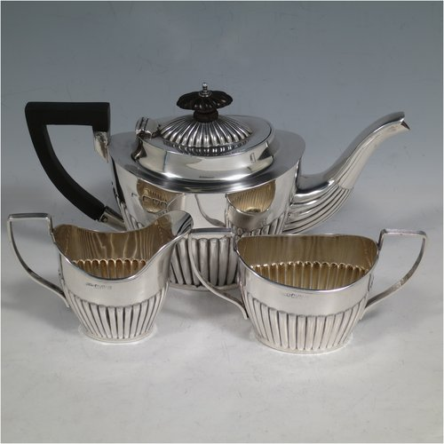 An Antique Edwardian Sterling Silver Bachelor three-piece tea set, having oval shaped bodies, fine half-fluted hand-chased decoration, reeded handles on the sugar & cream jug, and a  wooden handle & finial on the teapot, and all sitting on flat bases. Made by John Millward Banks of Chester in 1903/04. The dimensions of this fine hand-made antique silver tea set are length of teapot 21.5 cms (8.5 inches), height 12 cms (4.75 inches), and the total weight is approx. 403g (13 troy ounces).