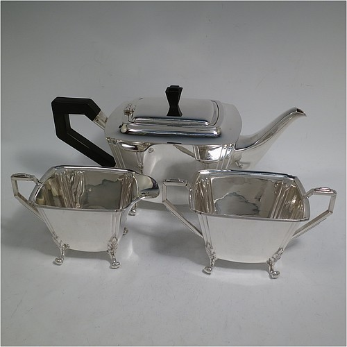 A very handsome and heavy Sterling Silver Art Deco three-piece tea set, consisting of a teapot, sugar bowl, and cream jug, in a plain rectangular panelled style with fluted corners, hand-cut stepped handles and matching finial, the teapot with a hinged lid, and all sitting on four cast scroll feet. Made by Joseph Gloster Ltd., of Birmingham in 1936. The dimensions of this fine hand-made Art Deco silver tea set are height of teapot 15 cms (6 inches), length 29 cms (11.3 inches), and it weighs a total of approx. 1,200g (39 troy ounces).