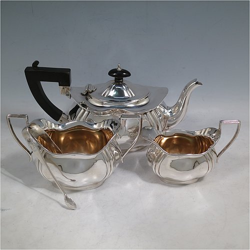 A Sterling Silver three-piece bachelor tea set, having oval shaped bodies, with hand-chased fluted corners, reeded handles and gold-gilt interiors on the sugar & cream jug, and a wooden handle & finial on the teapot, and all sitting on flat bases. Made in Birmingham in 1918. The dimensions of this fine hand-made silver tea set are length of teapot 24 cms (9.5 inches), height 12.5 cms (5 inches), and the total weight is approx. 671g (21.6 troy ounces). Please note there are NO sugar nips with this set.