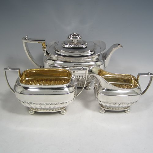 Antique Georgian sterling silver three-piece Regency style tea set, having a teapot, sugar bowl and cream jug. The bodies all hand-chased with half-fluted decoration, the sugar and creamer with gold-gilt interiors, the teapot with silver handle and finial, and an invisibly hinged lid, and all sitting on four ball feet. Made by Rebecca Emes and Edward Barnard of London in 1811 and 1813. The dimensions of this fine hand-made silver tea service are length of teapot 27 cms (10.5 inches), height 16 cms (6.3 inches), and it weighs a total of approx. 1,262g (41 troy ounces).