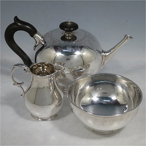An Antique Victorian Sterling Silver three-piece tea set, consisting of teapot, sugar bowl, and cream jug, in a round bullet style with top bands of hand-engraved floral decoration, the teapot with a flat hinged lid, a panelled straight spout, and a wooden finial and scroll handle, the cream jug with a scroll handle and sparrow-beak spout, and all sitting on collet feet. Made by Joseph & Edwards Bradbury of London in 1876. The dimensions of this fine hand-made antique silver tea set are height of teapot 12 cms (4.75 inches), length 20 cms (8 inches), and it weighs a total of approx. 550g (17.7 troy ounces). Please note that all three pieces are part-crested.
