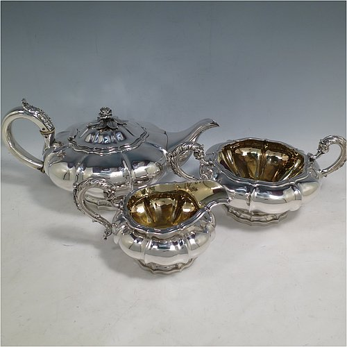 An Antique Georgian Sterling Silver three-piece tea set, having a teapot, sugar bowl and cream jug. The bodies all hand-chased with Melon style fluted decoration, the sugar and creamer with gold-gilt interiors and cast anthemion leaf handles, the teapot with silver insulated handle and cast rose finial, and all sitting on pedestal feet. Made by Rebecca Emes and John Barnard of London in 1826. The dimensions of this fine hand-made antique silver tea service are length of teapot 29 cms (11.5 inches), height 14 cms (5.5 inches), and it weighs a total of approx. 1,362g (44 troy ounces).