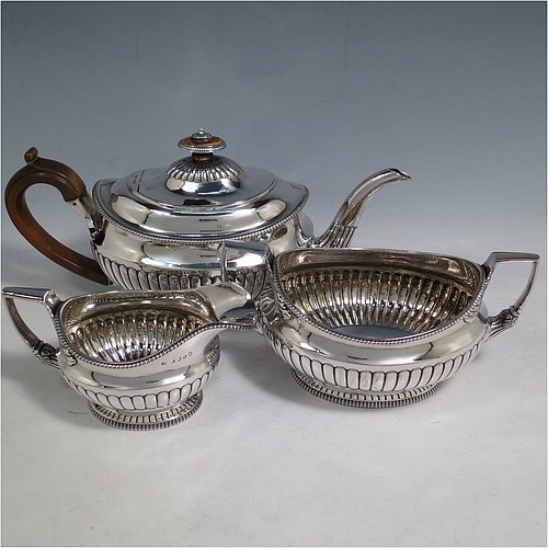 An Antique Georgian Sterling Silver three-piece early Regency style tea set, having a teapot, sugar bowl and cream jug. The oval bodies all hand-chased with half-fluted decoration, the sugar and creamer with gold-gilt interiors, the teapot with wooden handle and finial, and an invisibly hinged lid, all with applied gadroon borders, and all sitting on pedestal feet. Made by Daniel Pontifex London in 1805. The dimensions of this fine hand-made antique silver tea service are length of teapot 30 cms (11.75 inches), height 15 cms (6 inches), and it weighs a total of approx. 1,170g (38 troy ounces).