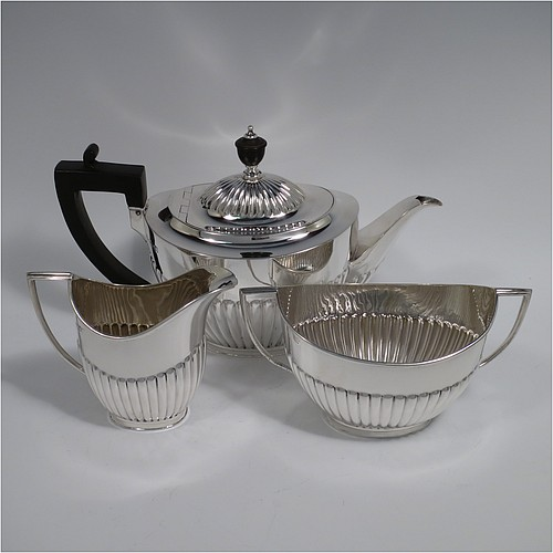 An Antique Edwardian Sterling Silver three-piece tea set in a Queen Anne style, having oval shaped bodies, fine half-fluted hand-chased decoration, reeded handles on the sugar & cream jug, and a wooden handle & finial on the teapot, and all sitting on flat bases. Made Goldsmiths and Silversmiths of London in 1904. The dimensions of this fine hand-made antique silver tea set are length of teapot 25 cms (9.75 inches), height 15 cms (6 inches), and the total weight is approx. 725g (23.4 troy ounces).