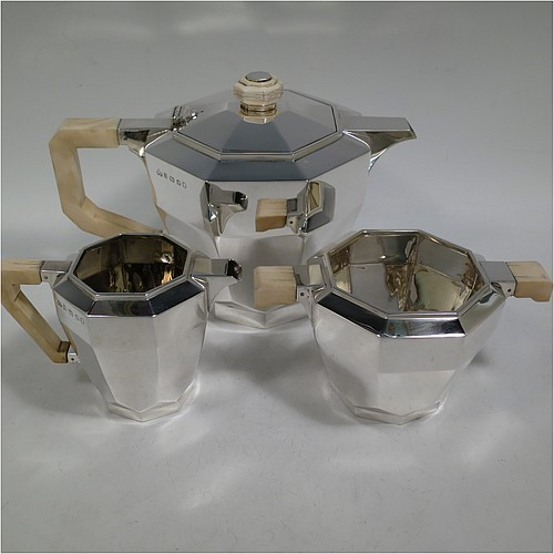 A very handsome and heavy Sterling Silver Art Deco three-piece tea set, consisting of a teapot, sugar bowl, and cream jug, in a plain octagonal panelled style with hand-cut handles and matching finial, the teapot with a hinged lid, and all sitting on octagonal collet feet. Made by Elkington and Co., of Birmingham in 1934/35. The dimensions of this fine hand-made Art Deco silver tea set are height of teapot 15 cms (6 inches), length 23 cms (9 inches), and it weighs a total of approx. 1,100g (35.5 troy ounces).