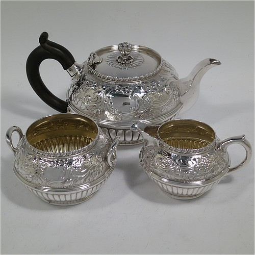 A very pretty Antique Victorian Sterling Silver three-piece bachelor tea set, having round bellied bodies with beautiful hand-chased floral and fluted decoration, the teapot with a flat hinged lid with a cast finial, a brown wooden scroll handle, and the cream and sugar bowl with loop handles and gold-gilt interiors, all sitting on collet feet. Made by the famous silversmith George Adams of London in 1889. The dimensions of this fine hand-made antique silver tea set are height of teapot 10 cms (4 inches), length of teapot 19 cms (7.5 inches), with a total weight of approx. 716g (23 troy ounces).