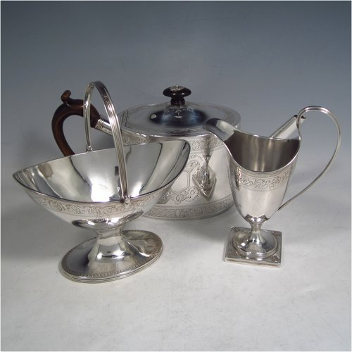 An Antique Georgian Sterling silver three-piece Neoclassical style tea set, having a teapot, sugar bowl and cream jug. The bodies all hand-engraved with bands of floral decoration and central cartouches, the sugar and creamer with applied reeded borders and pedestal feet, the teapot with wooden handle and finial, a flat base, and an invisibly hinged lid. Made by Samuel Meriton II of London in 1790/91. The dimensions of this fine hand-made silver tea service are length of teapot 27 cms (10.5 inches), height 14 cms (5.5 inches), and it weighs a total of approx. 830g (26.8 troy ounces). Please note that the teapot handle has had a small old repair close to the pins, but it does not affect the teapots usability, or deter from its prettiness.