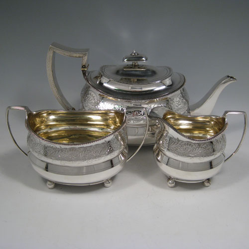 Antique Georgian sterling silver hand-engraved three-piece tea service with gadroon edges and sitting on ball feet. Made by Thomas Wallis II & Jonathan Hayne of London in 1810. The dimensions of this fine hand-made silver tea set are length of teapot 29 cms (11.5 inches), height 16 cms (6.25 inches), width 13.5 cms (5.25 inches), and it weighs a total of approx. 1,116g (36 troy ounces).