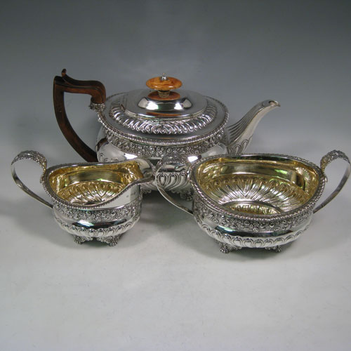 Antique Georgian sterling silver three-piece Regency style tea set, having a teapot, sugar bowl and cream jug. The bodies all hand-chased with roses and converging flute decoration, with applied gadroon borders, the sugar and creamer with gold-gilt interiors, the teapot with wooden handle and ivory finial, and an invisibly hinged lid, and all sitting on four cast foliate feet. Made by Charles Fox I of London in 1821. The dimensions of this fine hand-made silver tea service are length of teapot 29 cms (11.5 inches), height 17 cms (6.75 inches), and it weighs a total of approx. 1,260g (41 troy ounces).