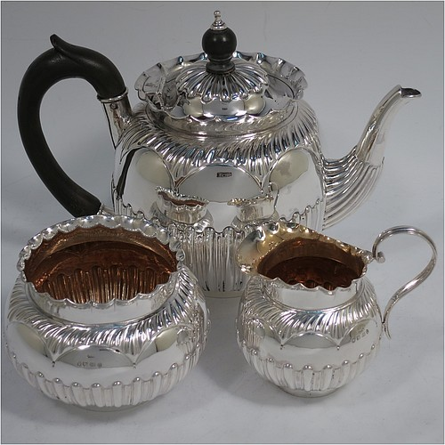 A very pretty Antique Victorian Sterling Silver three-piece bachelor tea set, having round bellied bodies with beautiful bands of hand-chased fluted decoration and wavy top borders, the teapot with a hinged lid and wooden finial, a wooden scroll handle, and the cream and sugar bowl with gold-gilt interiors, all sitting on collet feet. Made by Thomas Hayes of Birmingham in 1888. The dimensions of this fine hand-made antique silver bachelor tea set are height of teapot 14 cms (5.5 inches), length of teapot 19 cms (7.5 inches), with a total weight of approx. 474g (15.3 troy ounces).
