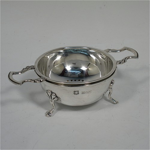 A Sterling Silver tea strainer and dregs bowl in a Georgian lemon strainer style, having a round hand-pierced bowl, cast scroll handles, and sitting on an original plain round dregs stand with three cast trefoil feet. Made by Barker Ellis Silver Co., of Birmingham in 1970. The dimensions of this fine hand-made silver tea strainer and stand are height 3 cms (1.25 inches), width across handles 11.5 cms (4.5 inches), and it weighs a total of approx. 73g (2.4 troy ounces).