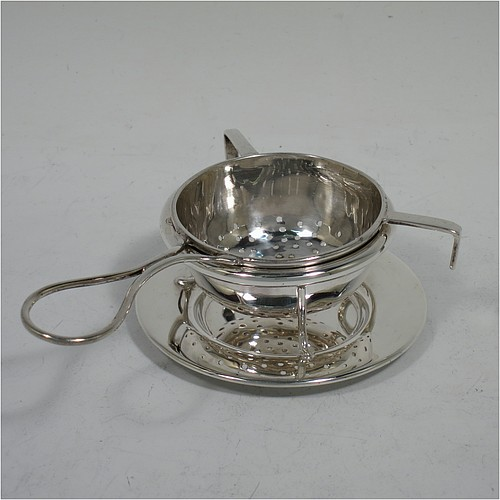A very stylish Sterling Silver tea strainer and stand, having a round hand-pierced bowl, with wire-work loop handle and two right-angled cup supports, all sitting on an original plain round dregs stand with a wire-work galleried holder on flat base. Made by James Round of Sheffield in 1921. The dimensions of this fine hand-made silver tea strainer and stand are height 4 cms (1.5 inches), length over handle 12 cms (4.75 inches), and it weighs a total of approx. 68g (2.2 troy ounces).