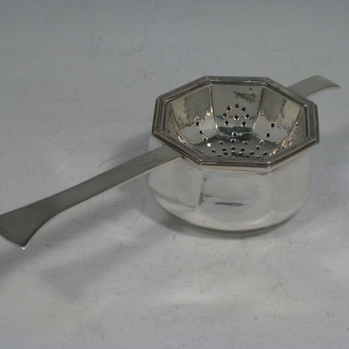 Sterling silver Arts and Crafts style tea strainer and bowl, having an octagonal strainer, reeded border, plain shaped handle, and sitting on its original octagonal shaped bowl. Made in London in 1949. Length 15.5 cms (6.25 inches), width of bowl 6.5 cms (2.5 inches). Total weight approx. 116g (3.7 troy ounces).