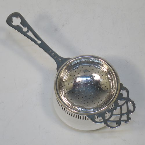 A pretty Sterling Silver tea strainer and bowl, having a hand-pierced handle, a round hand-pierced bowl with hand-cut side holder, and sitting on a plain round dregs stand with a band of piercing and bellied sides. Made by William Suckling Ltd., of Birmingham in 1933. The dimensions of this fine hand-made silver tea strainer & stand are length 14.5 cms (5.75 inches), diameter of stand 6 cms (2.3 inches), with a total weight of approx. 75g (2.4 troy ounces).