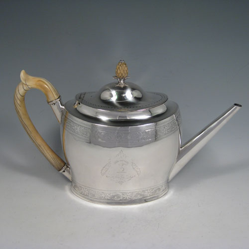 Antique Georgian sterling silver oval teapot with ivory scroll handle and pineapple finial, hinged lid with flat hinge, with top and bottom bands of hand-engraved floral decoration. Made by William Robinson of Edinburgh in 1797. Length 29 cms (11.5 inches), height 18.5 cms (7.25 inches). Weight approx. 580g (18.7 troy ounces). Please note that this piece is crested.