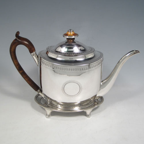 Antique Georgian sterling silver teapot on stand, having a hand-engraved oval body, with bands of floral decoration, a hinged domed lid with silver bound ivory finial, a wooden scroll handle, and sitting on its original stand with four flanged feet and reeded border. Made by Thomas Robins of London in 1800. The dimensions of this fine hand-made silver teapot on stand are length 28 cms (11 inches), height (on stand) 19 cms (7.5 inches), and it weighs approx. 543g (17.5 troy ounces).