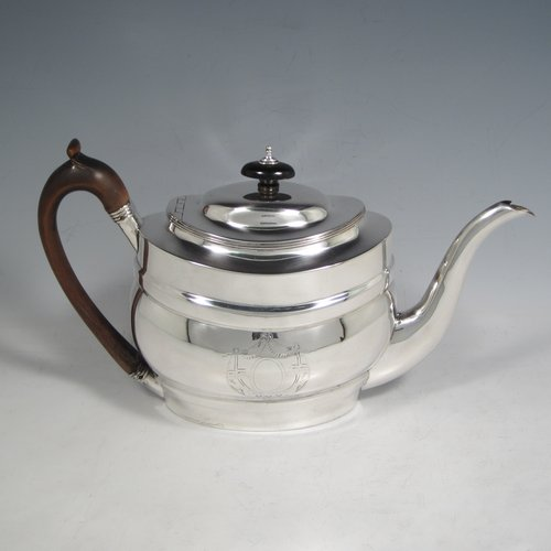 Antique Georgian sterling silver oval teapot, having a plain baluster body, with hand-engraved neoclassical style engraving around vacant cartouches either side, a hand-cut wooden handle and finial, a scroll spout, and with a flat-hinged domed lid. Made by Soloman Hougham of London in 1802. The dimensions of this fine hand-made silver teapot are length 28 cms (11.0 inches), height 17 cms (6.75 inches), and it weighs approx. 434g (14 troy ounces).