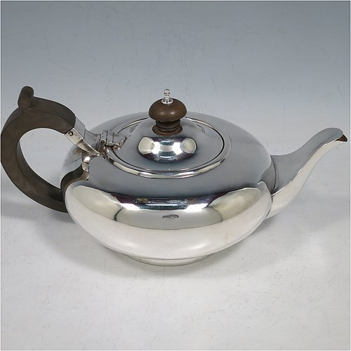 A Sterling Silver Scottish bachelor size teapot, in a plain round bellied style, having a hinged lid with wooden finial, a wooden insulated handle, a plain curved spout, and all sitting on a collet foot. Made by Robert Stewart of Glasgow in 1928. The dimensions of this fine hand-made Scottish silver teapot are height 10 cms (4 inches), length 21 cms (8.25 inches), and it weighs approx. 320g (10.3 troy ounces).