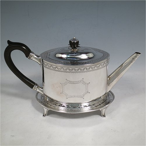 An Antique Georgian Sterling Silver teapot on stand, having a hand-engraved oval body, with bands of floral decoration, a hinged domed lid with silver bound wooden finial and flat hidden hinge, a wooden scroll handle, and sitting on its original stand with four flanged feet and reeded border. Made by Joseph Scammell of London in 1790. The dimensions of this fine hand-made antique silver teapot on stand are length 28 cms (11 inches), height (on stand) 16 cms (6.25 inches), and it weighs approx. 527g (17 troy ounces).
