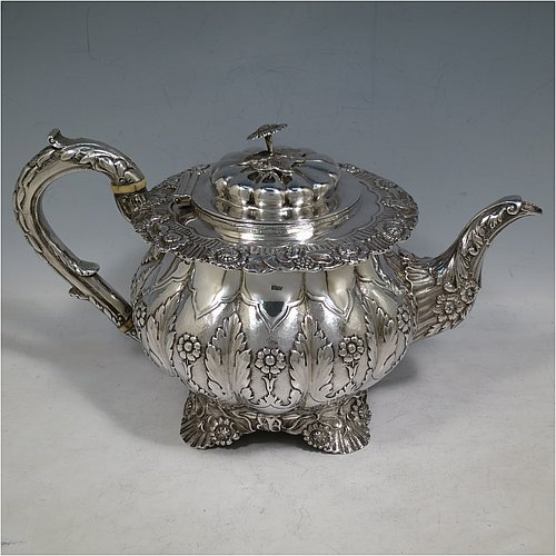 An Antique Victorian Sterling Silver teapot, having a round bellied body with hand-chased floral and Anthemion leaf decoration, a silver insulated scroll handle, a domed & fluted hinged lid with cast silver flower finial, and sitting on four cast foliate and scalloped feet. Made by Joshua Vander of London in 1899. The dimensions of this fine hand-made antique silver teapot are length 28 cms (11 inches), height 15 cms (6 inches), and it weighs approx. 930g (31 troy ounces).
