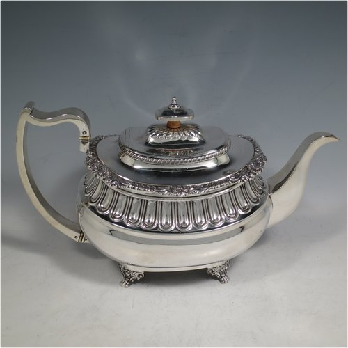 An Antique Georgian Sterling silver Regency style teapot, having a rectangular baluster body with hand-chased half-fluting, an applied shell and gadroon border, a silver insulated scroll handle, a hinged lid with silver finial, and all sitting on four cast foliate & paw feet. Made by William Bateman of London in 1816. The dimensions of this fine hand-made silver teapot are height 17 cms (6.75 inches), length 30 cms (11.75 inches), and it weighs approx. 781g (25 troy ounces).