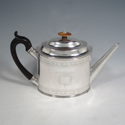 Antique Georgian sterling silver teapot, having an oval straight-sided body with hand-engraved bands of floral work and cartouche on both sides, a straight tapering spout, wooden scroll handle and ivory finial, an invisibly hinged domed lid, and sitting on a flat base with applied reeded border. Made by Peter and Anne Bateman of London in 1795. The dimensions of this fine hand-made antique silver teapot are length 27 cms (10.5 inches), height 16 cms (5.25 inches), and it weighs approx. 410g (13 troy ounces).