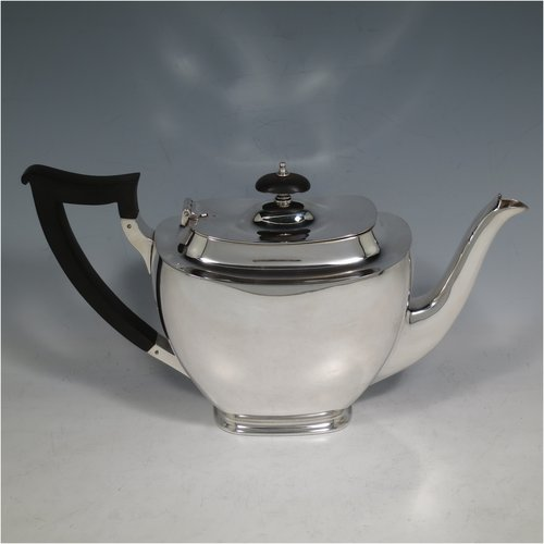 A Sterling Silver teapot, in a rectangular style having a plain body with rounded corners, with a hinged lid and wooden finial, a wooden insulated handle, and sitting on collet feet. Made by James Dixon & Sons of Sheffield in 1942. The dimensions of this fine hand-made silver teapot are height of 15 cms (6 inches), length 27 cms (10.5 inches), and it weighs a total of approx. 650g (21 troy ounces).