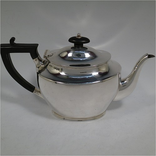 A handsome Sterling Silver teapot, in a plain oval  bellied style, having a hinged domed lid with a  wooden finial, a wooden insulated handle, a plain curved spout, and all sitting on a collet foot. Made by Henry Stratford of Sheffield in 1922. The dimensions of this fine hand-made silver teapot are height 15 cms (6 inches), length 26.5 cms (10 inches), and it weighs approx. 395g (12.7 troy ounces).