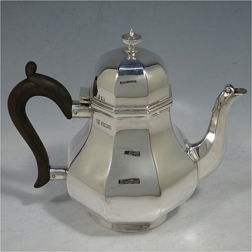 An Antique Edwardian Sterling Silver George I style bachelor sized teapot, having a plain panelled bellied body, with a wooden scroll handle, a hinged domed lid with cast finial, a panelled spout, and all sitting on a collet foot. Made by Fordham & Faulkner of Sheffield in 1906. The dimensions of this fine hand-made antique silver bachelor teapot are height 15 cms (6 inches), length 18 cms (7 inches), and the weight is approx. 280g (9 troy ounces).