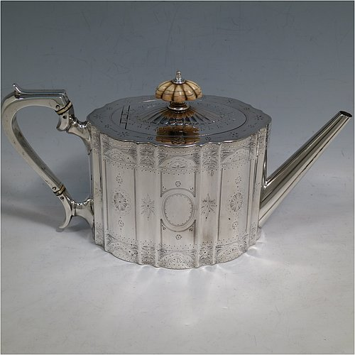 An Antique Victorian Sterling Silver teapot with straight-sided and shaped fluted body, a straight fluted spout, an ivory finial and silver scroll handle, an oval domed invisibly hinged lid, and bright-cut engraved floral decoration. Made by W. & G. Sissons of London in 1868. The dimensions of this fine hand-made antique silver teapot are length 25.5 cms (10 inches), height 19 cms (7.5 inches), width 13.5 cms (5.3 inches), and it weighs approx. 487g (15.7 troy ounces).