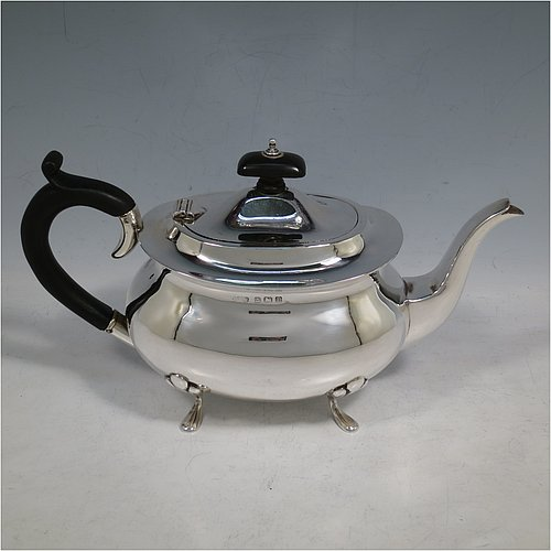 A Sterling Silver teapot, having a plain rounded rectangular and bellied body, a hinged and domed lid with wooden finial, a wooden insulated scroll handle, and sitting on four plain feet with foliate shoulders. Made in Birmingham in 1929. The dimensions of this fine hand-made silver teapot are height 14 cms (5.5 inches), length 25.5 cms (10 inches), and it weighs approx. 375g (12 troy ounces).