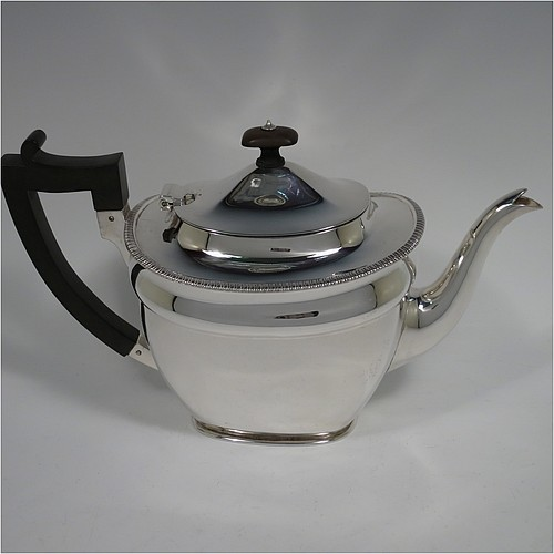 An Antique Edwardian Sterling Silver teapot, in a rectangular style having a plain body with an applied gadroon upper border, with tapering sides and rounded corners, a hinged domed lid and wooden finial, a wooden insulated handle, and sitting on a collet foot. Made by Marples and Co., of Sheffield in 1909. The dimensions of this fine hand-made antique silver teapot are height 16 cms (6.3 inches), length 27 cms (10.5 inches), and it weighs a total of approx. 640g (21 troy ounces).