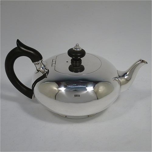 A rare Antique Georgian Sterling Silver bachelor size teapot, in a plain round bellied style, having a flat invisibly hinged lid with wooden finial, a wooden insulated handle, a plain curved spout, and all sitting on a collet foot. Made by William Edwards of London in 1824. The dimensions of this fine hand-made antique silver bachelor teapot are height 9.5 cms (3.75 inches), length 20 cms (8 inches), and it weighs approx. 350g (11.3 troy ounces).