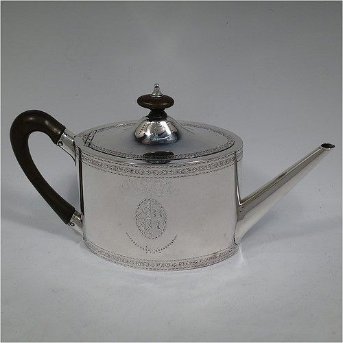 A very handsome Neoclassical style Antique Georgian Sterling Silver teapot, having an oval straight-sided body with hand-engraved upper and lower bands of floral work, with oval engraved cartouches on both sides, a straight tapering spout, a wooden scroll handle and oval finial, an invisibly hinged domed lid with matching engraving, and all sitting on a flat base. Made by William Turton of London in 1785, with a rare Incuse Duty Mark. The dimensions of this fine hand-made antique silver teapot are length 27 cms (10.5 inches), height 15 cms (6 inches), and it weighs approx. 350g (11.3 troy ounces). Please note that this item is crested.