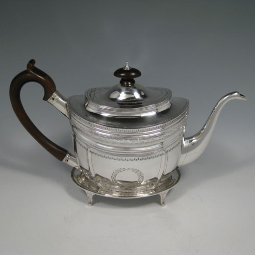 Antique Georgian sterling silver teapot on stand, having a hand-engraved oval body, a hinged domed lid with wooden finial, a wooden scroll handle, and sitting on its original stand with four flanged feet. Made by George Brasier of London in 1800. Length 29 cms (11.5 inches), height (on stand) 18 cms (7 inches). Weight approx. 527g (17 troy ounces).