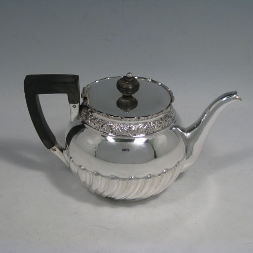 Antique Victorian sterling silver Bachelor teapot, having a round half swirl-fluted body, wooden finial and handle, and a  hinged lid below which is a band of hand-chased floral decoration. Made by George Maudsley Jackson of London in 1889. Please note that the main hallmarks on the body are rubbed, but the hallmarks underneath the lid are very crisp. Length 19 cms (7.5 inches), height 11 cms (4.25 inches), diameter 11 cms (4.25 inches). Weight approx. 235g (7.6 troy ounces).