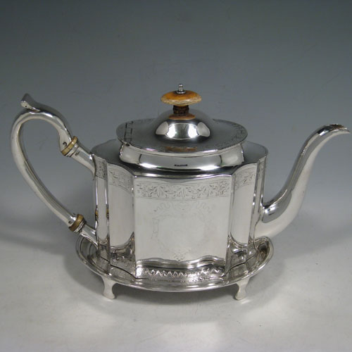 Antique Georgian sterling silver teapot on stand, having a hand-engraved straight-sided and shaped oval body, a hinged domed lid with ivory finial, an original silver scroll handle, and sitting on its original stand with four flanged feet. Made by Robert Gaze of London in 1794. Length 29 cms (11.5 inches), height (on stand) 18 cms (7 inches). Weight approx. 790g (25.5 troy ounces).
