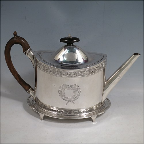 An Antique Georgian Sterling Silver teapot on stand, having a hand-engraved oval body, with bands of floral decoration, a hinged domed lid with wooden finial and flat hidden hinge, a wooden scroll handle, and sitting on a matching stand with four flanged feet and reeded border. The teapot made by Frances Purton of London in 1794, and the stand by Timothy Renou of London in 1795. The dimensions of this fine hand-made antique silver teapot on stand are length 26 cms (10.25 inches), height (on stand) 16 cms (6.25 inches), and it weighs approx. 475g (15.2 troy ounces).