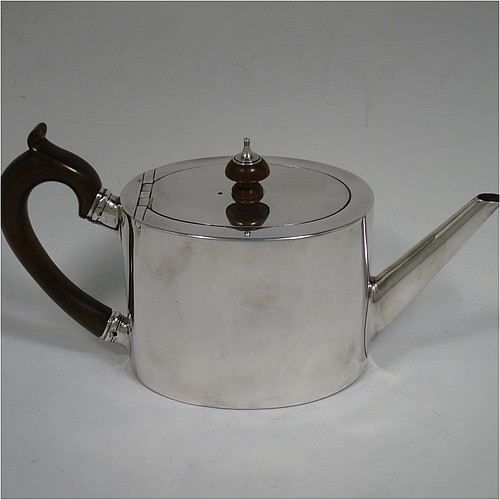 A very handsome Neoclassical style Antique Georgian Sterling Silver teapot in a Bachelor size for two people, having a very plain oval straight-sided body, a straight tapering spout, a wooden scroll handle and round finial, an invisibly hinged flat lid, and all sitting on a flat base. Made by Charles Aldridge and Henry Green of London in 1780. The dimensions of this fine hand-made antique silver bachelor teapot are length 23 cms (9 inches), height 12 cms (4.75 inches), and it weighs approx. 310g (31 troy ounces).