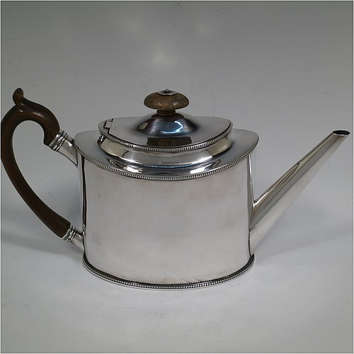 A very handsome Neoclassical style Antique Georgian Sterling Silver teapot, having a very plain oval straight-sided body with applied bead-edged borders, a straight tapering spout, a wooden scroll handle and oval finial, an invisibly hinged domed lid, and all sitting on a flat base. Made by Thomas Streetin of London in 1791. The dimensions of this fine hand-made antique silver teapot are length 27.5 cms (10.75 inches), height 15 cms (6 inches), and it weighs approx. 465g (15 troy ounces).