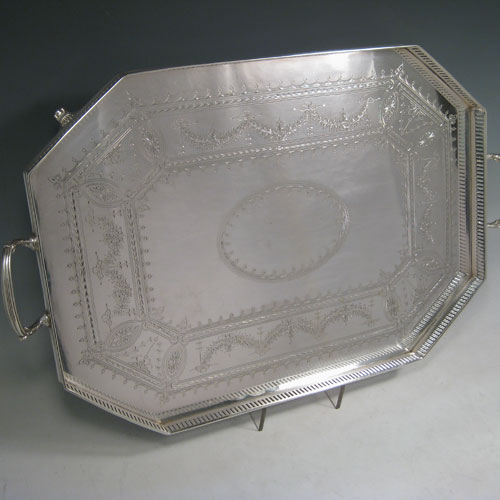 Antique Victorian silver plated tray, having an octagonal sided body, a hand-engraved ground with geometrical and floral swag decoration, a hand-pierced gallery edge, two cast reeded handles, and sitting on four cast reeded flange feet. This beautiful silver-plated tray was made by Latham and Morton in ca. 1880. The dimensions of this fine hand-made silver plated tea tray are length (inc. handles) 53 cms (21 inches), width 33 cms (13 inches).