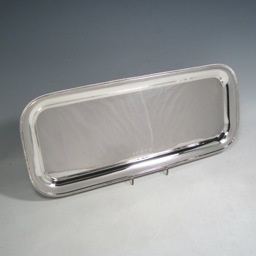 Sterling silver sandwich tray, having a rectangular body with rounded corners, a very plain ground, a raised  border with an applied gadroon edge, and sitting on a flat base. Made by the Barker Brothers  of Birmingham in 1921. The dimensions of this fine hand-made silver sandwich tray are length 39.5 cms (15.5 inches), width 17 cms (6.75 inches), and it weighs approx. 640g (20.6 troy ounces).