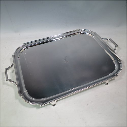 An Antique Edwardian heavy Sterling Silver Georgian style tea tray, having a rectangular body with rounded cut corners, a very plain ground with a centrally engraved crest, an applied reeded border, two cast scroll side-handles, and sitting on four cast flanged feet. Made by Thomas Bradbury of London in 1905. The dimensions of this fine hand-made antique silver tray are length (inc. handles) 53 cms (20.75 inches), width 35 cms (13.75 inches), and it weighs approx. 2,325g (75 troy ounces). Please note that this item is crested.