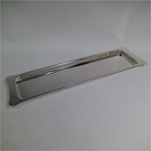 An Antique Edwardian Sterling Silver sandwich tray, having a long plain rectangular body, a very plain ground, a plain border with lobed corner handles, and sitting on a flat base. Made by Heath and Middleton of Birmingham in 1908. The dimensions of this fine hand-made antique silver sandwich tray are length 46 cms (18 inches), width 13.5 cms (5.25 inches), and it weighs approx. 506g (16.3 troy ounces).