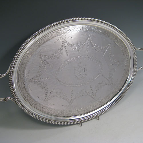Antique Georgian sterling silver oval two-handled tea tray with beautifully hand-engraved floral and swag decoration, and cast gadroon border. This handsome sterling silver tray was made by William Bennett of London in 1805. The dimensions of this fine hand-made silver tray are length inc. handles 53 cms (21 inches), width 33 cms (13 inches), and it weighs approx. 1,550g (50 troy ounces). Please note that this item is crested in the central cartouche.