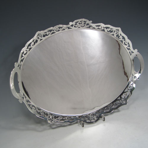 Sterling silver tea tray, having an oval body with a very plain ground, a raised gallery border with hand-pierced scroll decoration, two integral side-handles, and sitting on a flat base. Made by J. Gloster Ltd., of Birmingham in 1932. The dimensions of this fine hand-made silver tray are length (inc. handles) 50 cms (19.75 inches), width 35.5 cms (14 inches), and it weighs approx. 1,300g (42 troy ounces).